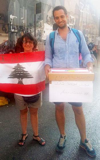 شاب يحمل صندوق اقتراع ويجول بين المتظاهرين في بيروت