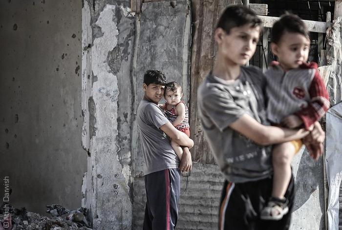 صور من غزة - صبي يحمل أخيه الطفل